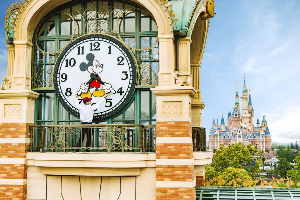 """ALMOST TIME - A Shanghai Disneyland cast member prepares the theme park's iconic """"Mickey Avenue"""" clock in advance of the Grand Opening of Shanghai Disney Resort on June 16, 2016 with the spectacular backdrop of the world's largest Disney castle, The Enchanted Storybook Castle. Shanghai Disney Resort is a world-class family entertainment destination, imagined and created especially for the people of China. Ideal for multiple-day visits, the resort consists of Shanghai Disneyland, a theme park with magical experiences for guests of all ages; two richly themed hotels; Disneytown, an international shopping, dining and entertainment district; and Wishing Star Park, a recreational area with peaceful gardens and a glittering lake. The resort's hotels are the elegant, 420- room Shanghai Disneyland Hotel and the playful, 800-room Toy Story Hotel. Shanghai Disney Resort is a joint venture between The Walt Disney Company and Shanghai Shendi Group comprised of two owner companies (Shanghai International Theme Park Company Limited and Shanghai International Theme Park Associated Facilities Company Limited) and a management company (Shanghai International Theme Park and Resort Management Company Limited). (Matt Stroshane, photographer)"""