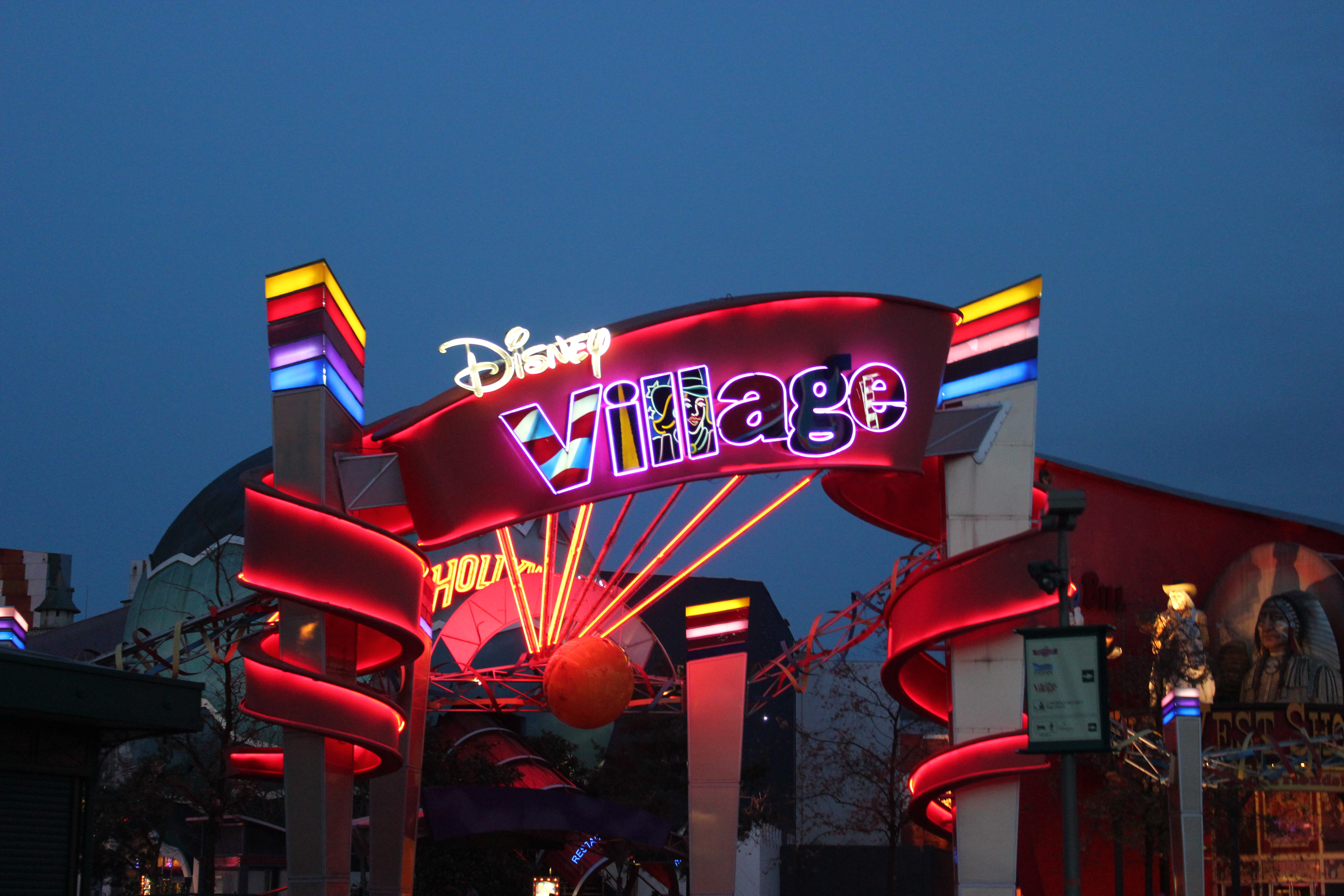 Disney Village sign lit up on a summers night