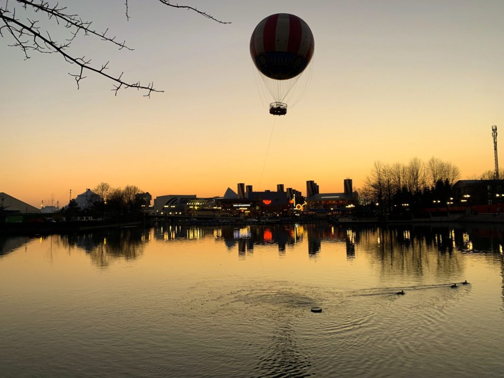 The Panoramagique balloon flying over Disneyland Paris at sunset.